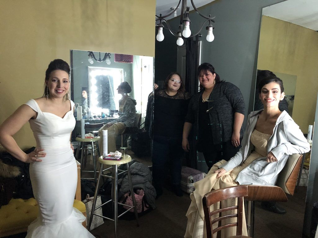 Behind the scenes group shot of models and hairstylists on set of a stylized bridal photoshoot.