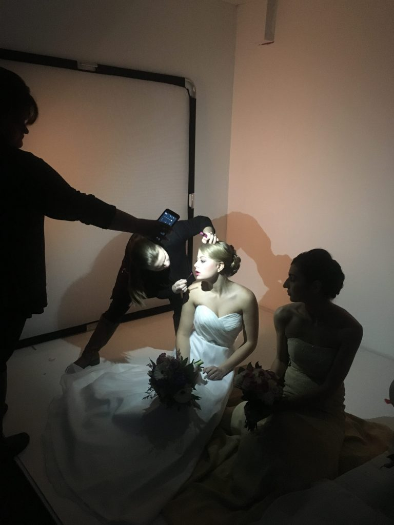 Lauren of LA Page Makeup touching up a model's lips in between shots on the set of a stylized bridal photoshoot.