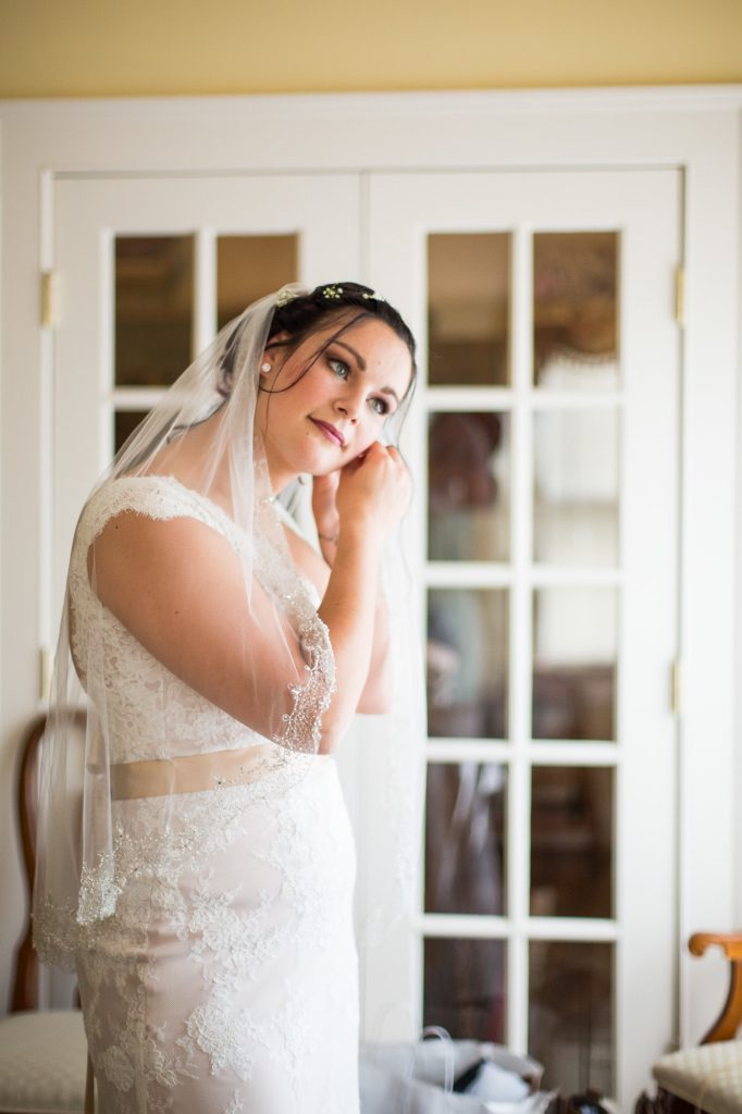Beautiful bride getting ready before walking down the aisle at Candlelight Farms Inn.