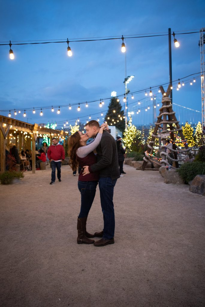 The beautiful sky, the festive Christmas trees, the loving kiss. What's not to adore about this engagement session picture?!
