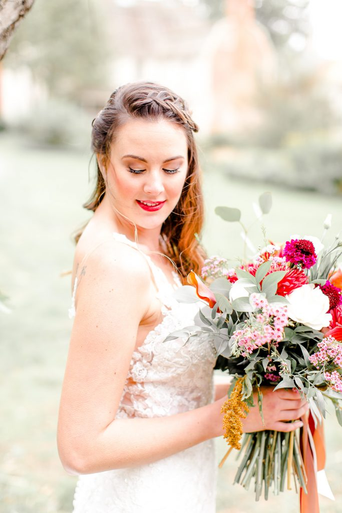 The bride enjoying her flawless makeup and hair, beautiful gown, and fabulous flowers at her rustic Webb Barn wedding in Wethersfield, CT.