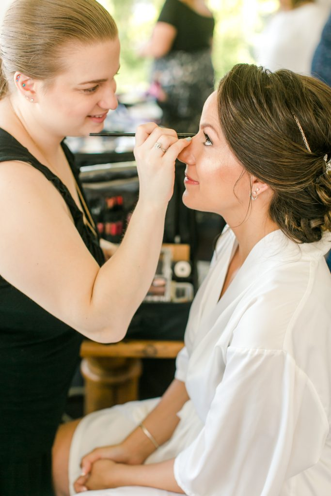 Lauren, the owner of LA Page Makeup, completing the bride's makeup at her cottage in Branford, CT.