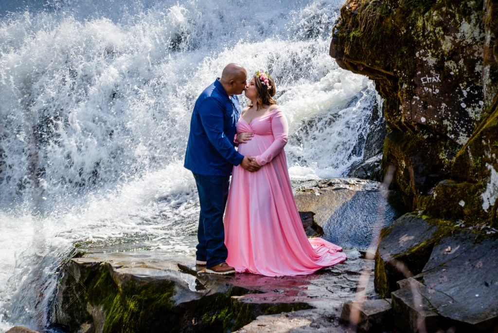 The happy parents-to-be kissing by a gorgeous waterfall at Wadsworth Falls State Park in Middletown, CT.
