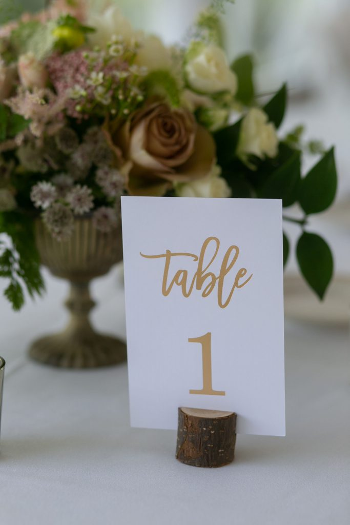 The calligraphy on these table numbers is elegant and works perfectly for this gold themed wedding!
