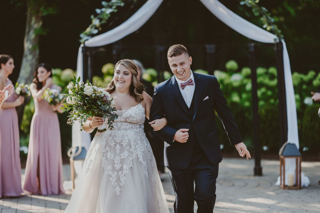 The happy bride and groom take their first walk down the aisle as husband and wife at Bill Miller's Castle in Branford, CT.