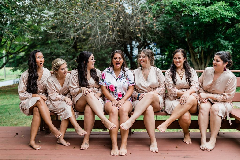Johnna's bridal party looked adorable in their blush pink robes and big smiles as they celebrate her rustic glam wedding at Tyrone Farm in Pomfret, CT.