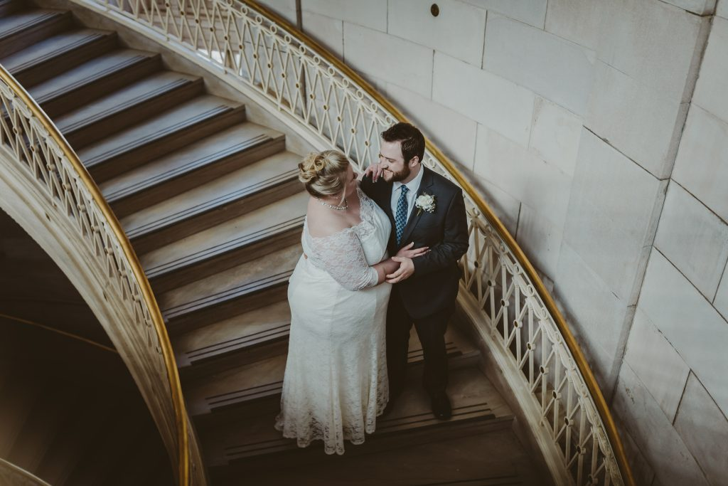 bride and groom pose on a stairwell