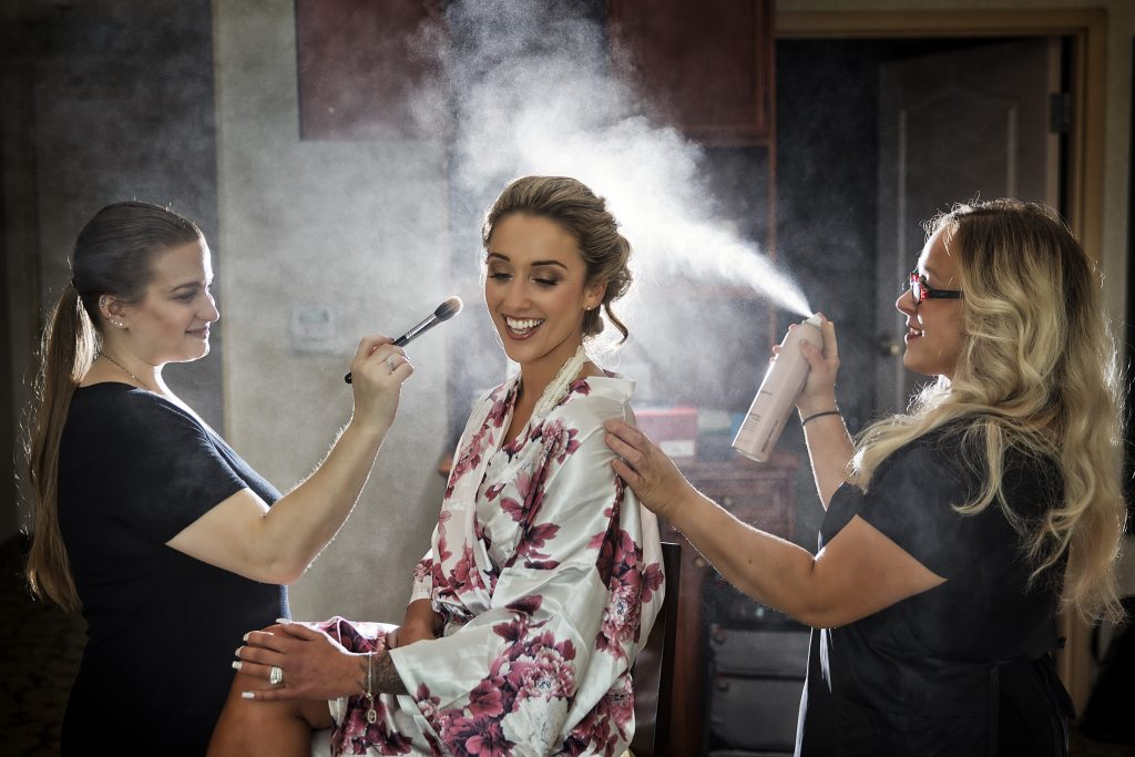 Bride getting hairspray and makeup touch ups from her wedding makeup artist and bridal hair stylist on her wedding day.